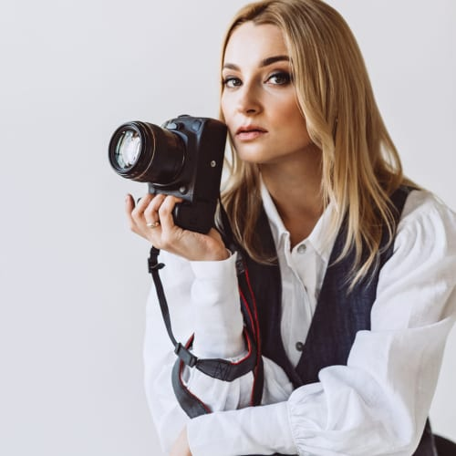 A beautiful woman photographer in a denim casual outfit and a white blouse with voluminous sleeves with a camera in her hands. Hobbies. Soft selective focus.